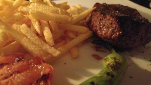 Argentinisches Steak in Nahaufnahme, gegrillter Tomate und Peperoni sowie Pommes Frites